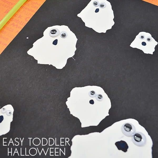 Straw blown white paint on black paper to make spooky ghosts. Halloween craft ideas for toddlers.
