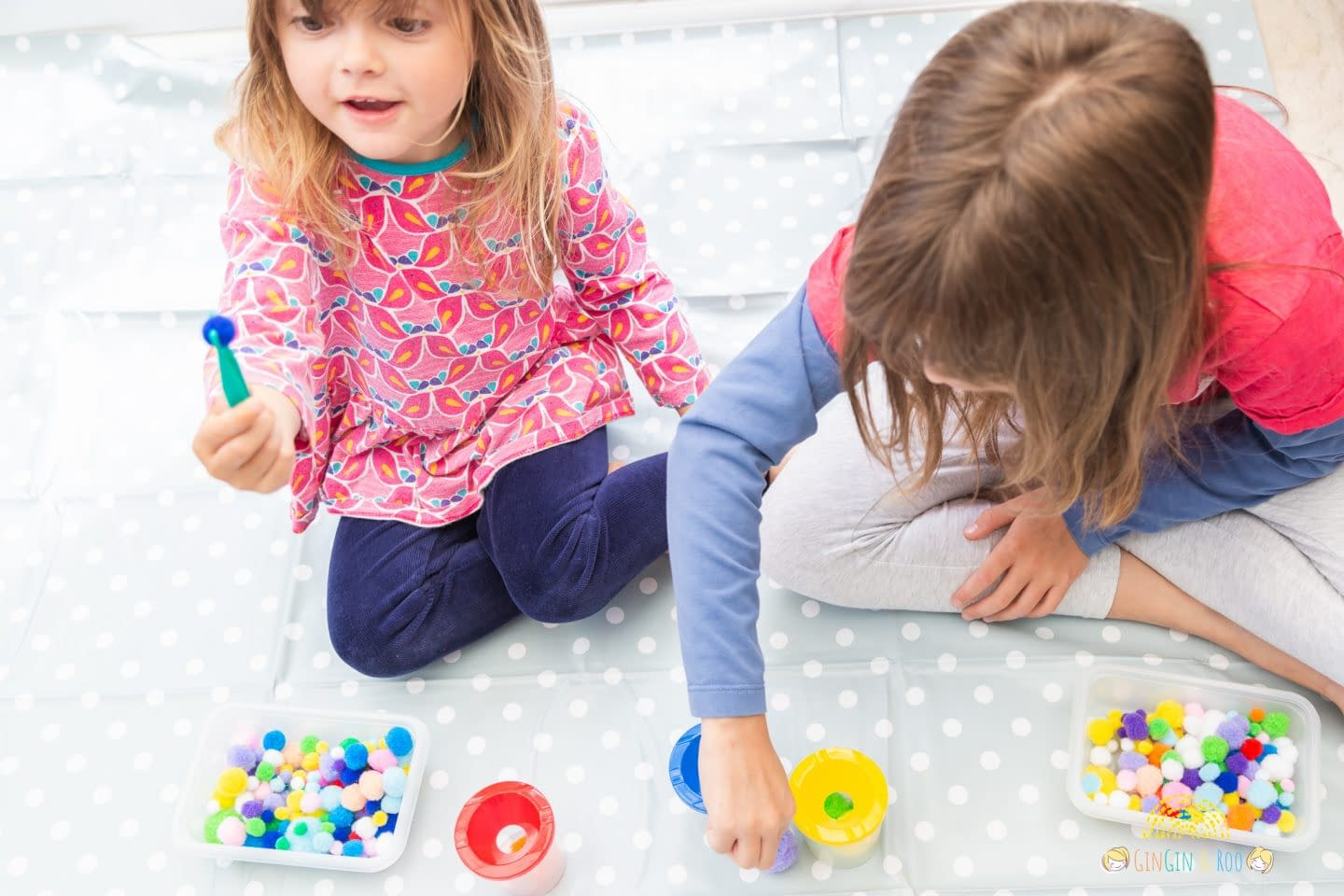 Two girls playing pom pom pick-up Colourful pompoms, cups and forceps for a toddler or preschooler game by GinGin & Roo