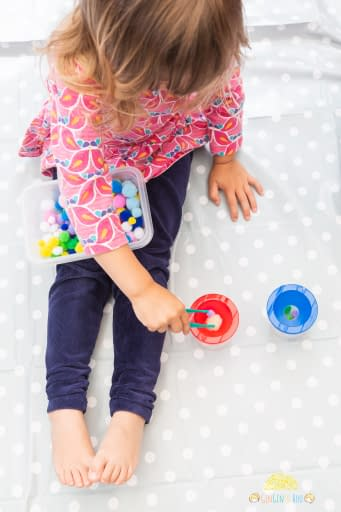 preschooler girl playing pom pom pick-up Colourful pompoms, cups and forceps for a toddler or preschooler game by GinGin & Roo