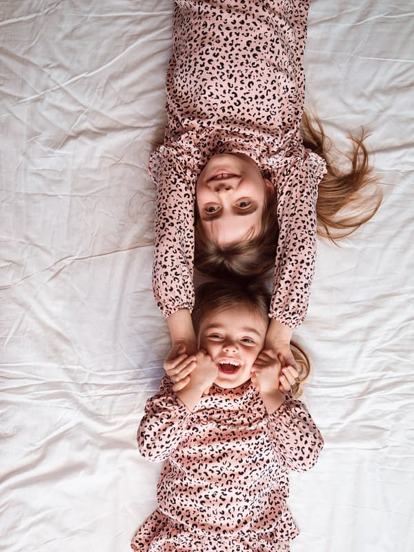 GinGin and Roo - child sisters laughing on white background